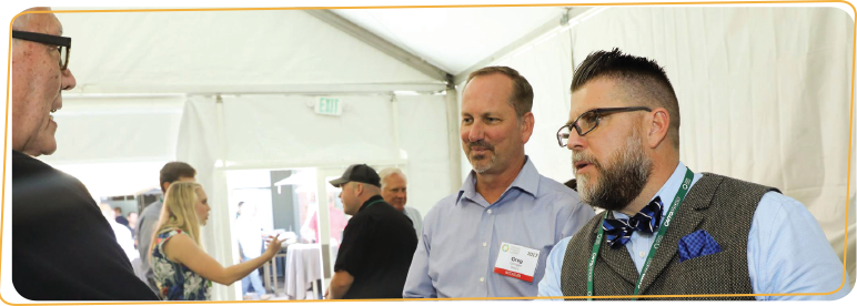 Greg Corrigan and Michael Schutt from Raley's meet with an exhibitor
