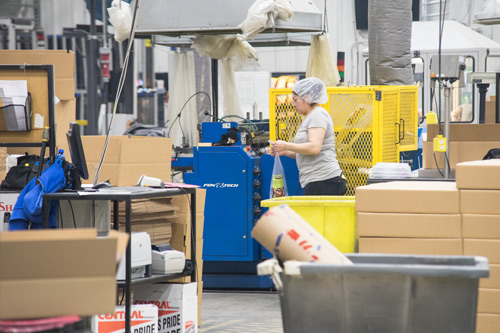 A Volm employee packing an item on the line