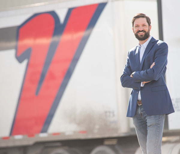 Daniel Mueller standing proudly by a company truck
