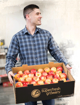 Alex Fickes carrying a box of Superfresh Growers® apples