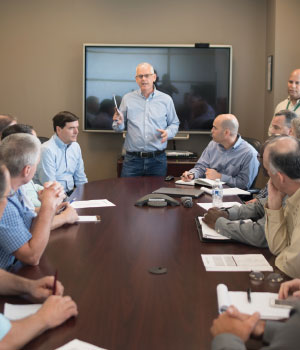 John Gates (standing, left), leads meeting for buying and sales staff with Executive Vice President Kevin Jones (standing, right)