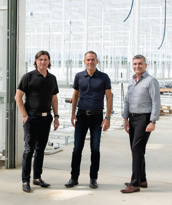 Danny Mucci, Bert Mucci, and Joe Spano standing in the doorway to their new greenhouse expansion for hydroponically grown  Smuccies™  strawberries