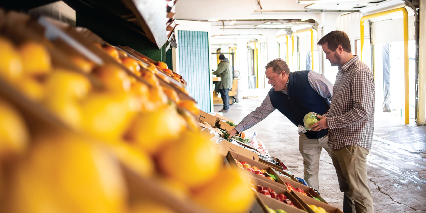 Chase and Trevor inspecting produce at a terminal outside the Tom Lange Family of Companies' Marietta, Georgia, office